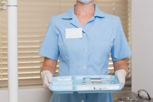 Dental assistant in blue holding tray of tools at the dental clinic
