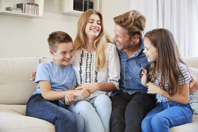 Smiling Family Relaxing On Sofa At Home Together